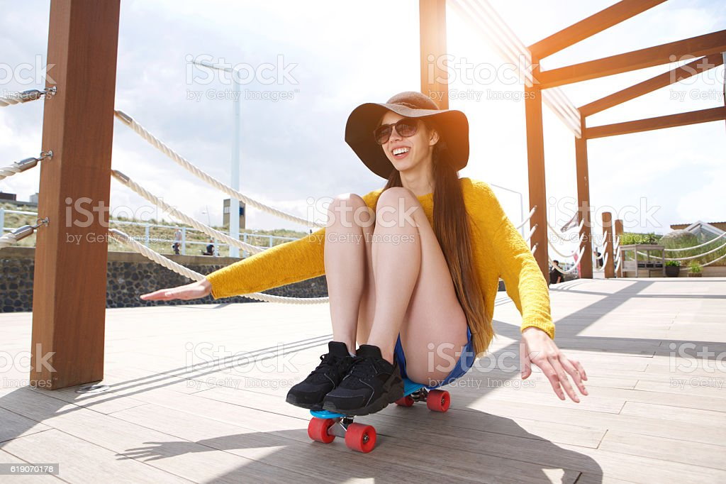 Smiling young woman having fun sitting on skateboard stock photo
