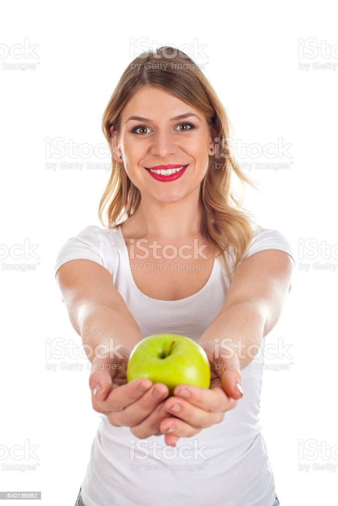 Smiling young woman holding a green apple stock photo