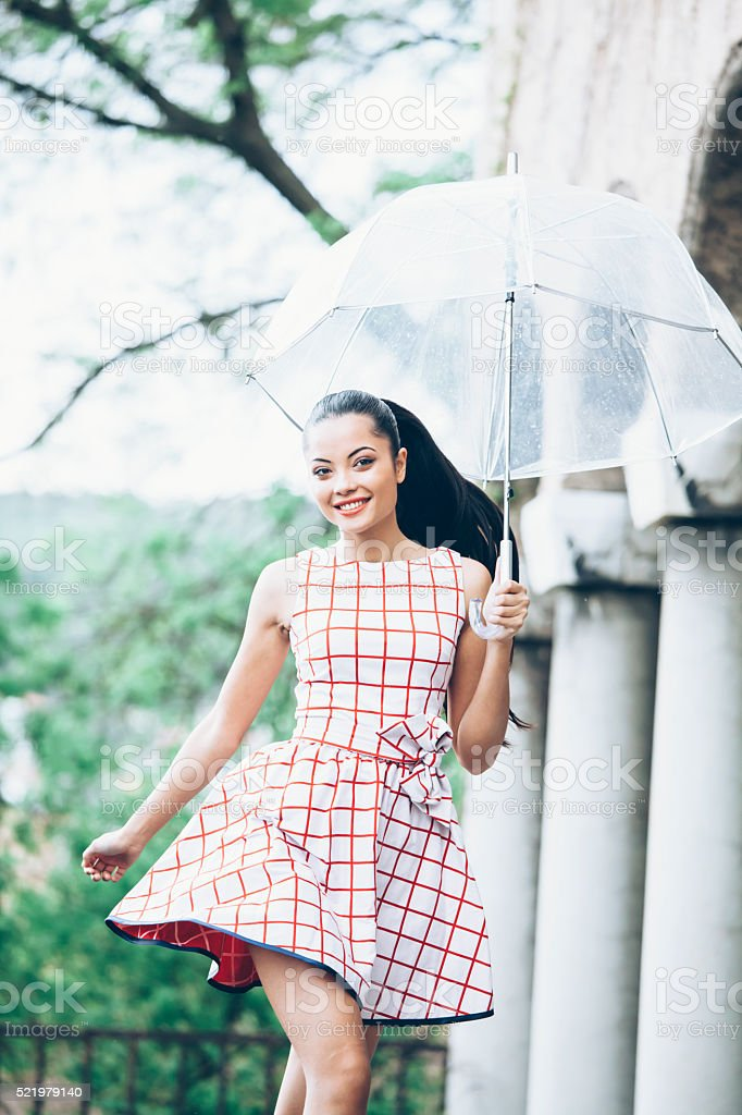 Smiling young woman holding an umbrella stock photo