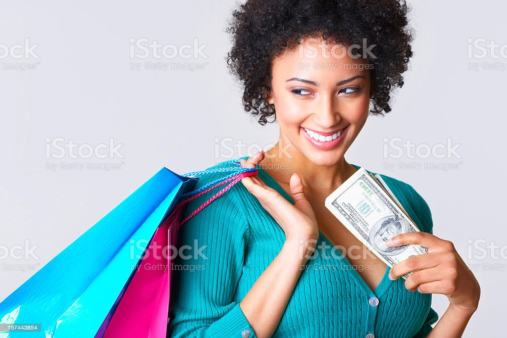 smiling young woman holding bunch of money, carrying shopping bags royalty-free stock photo