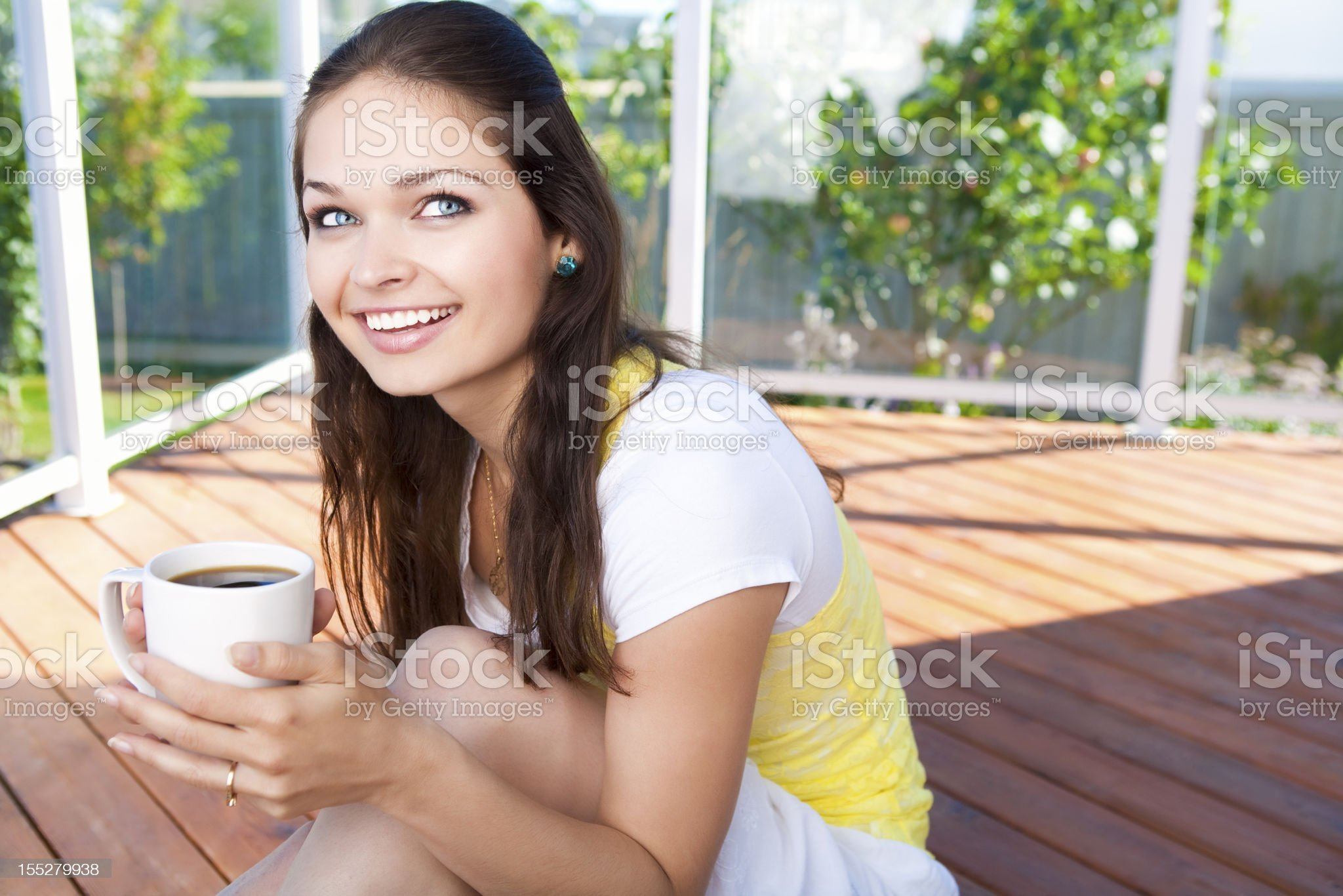 Smiling young woman holding coffee cup royalty-free stock photo