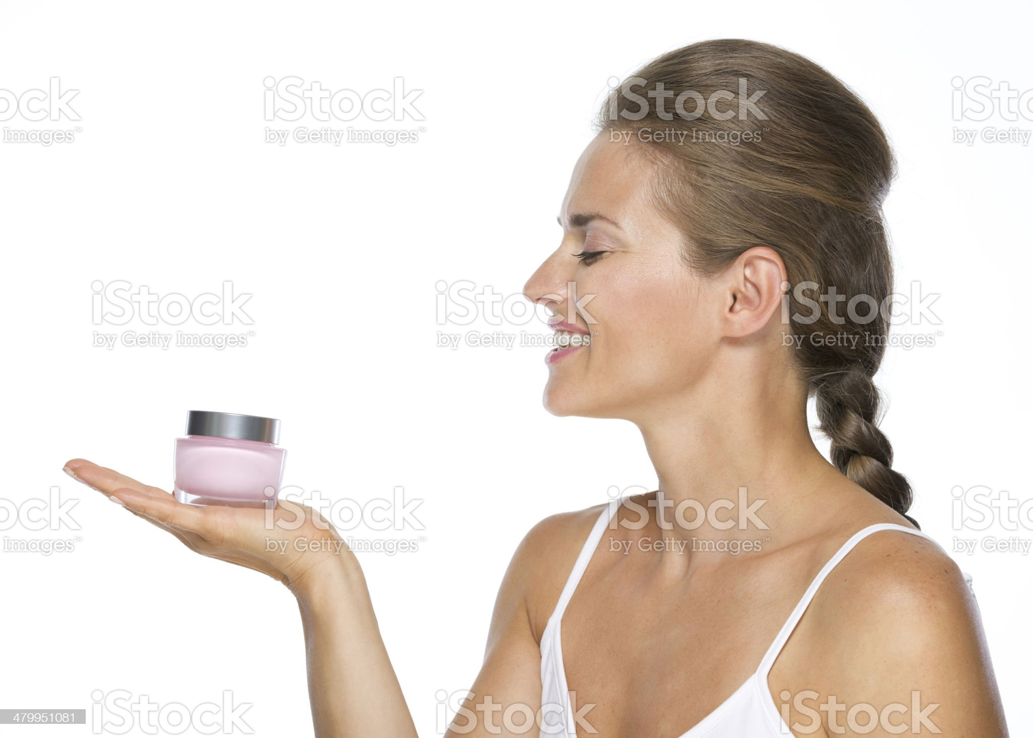 smiling young woman holding cream bottle royalty-free stock photo
