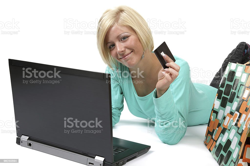 Smiling young woman holding credit card using laptop stock photo