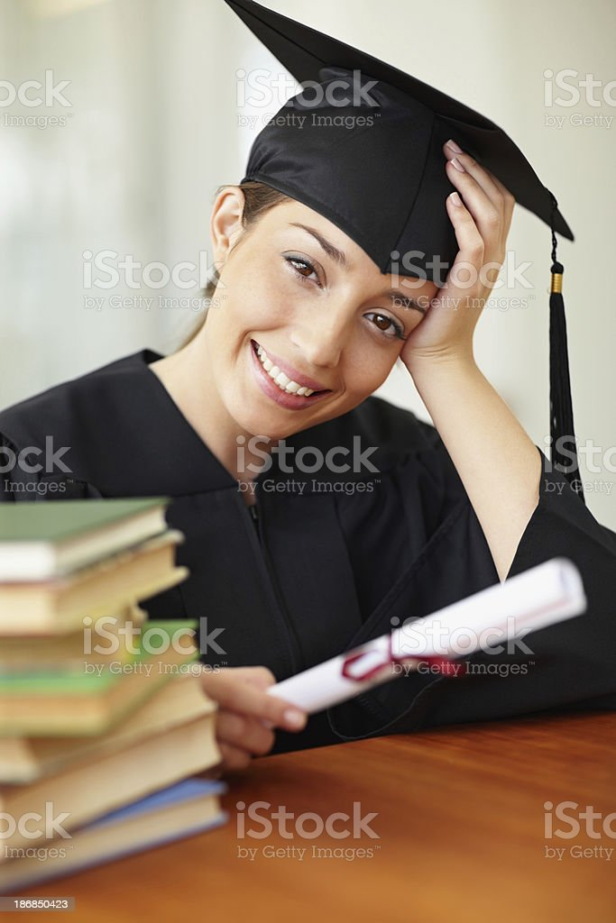 Smiling young woman holding graduation certificate royalty-free stock photo