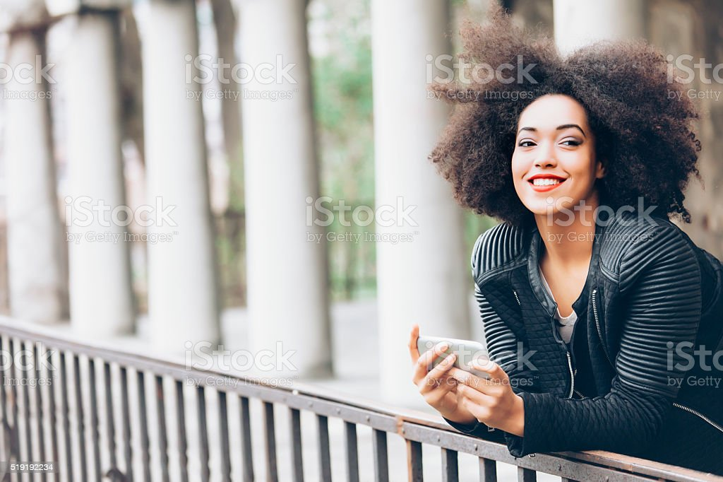 Smiling young woman holding smart phone and laening on fence stock photo