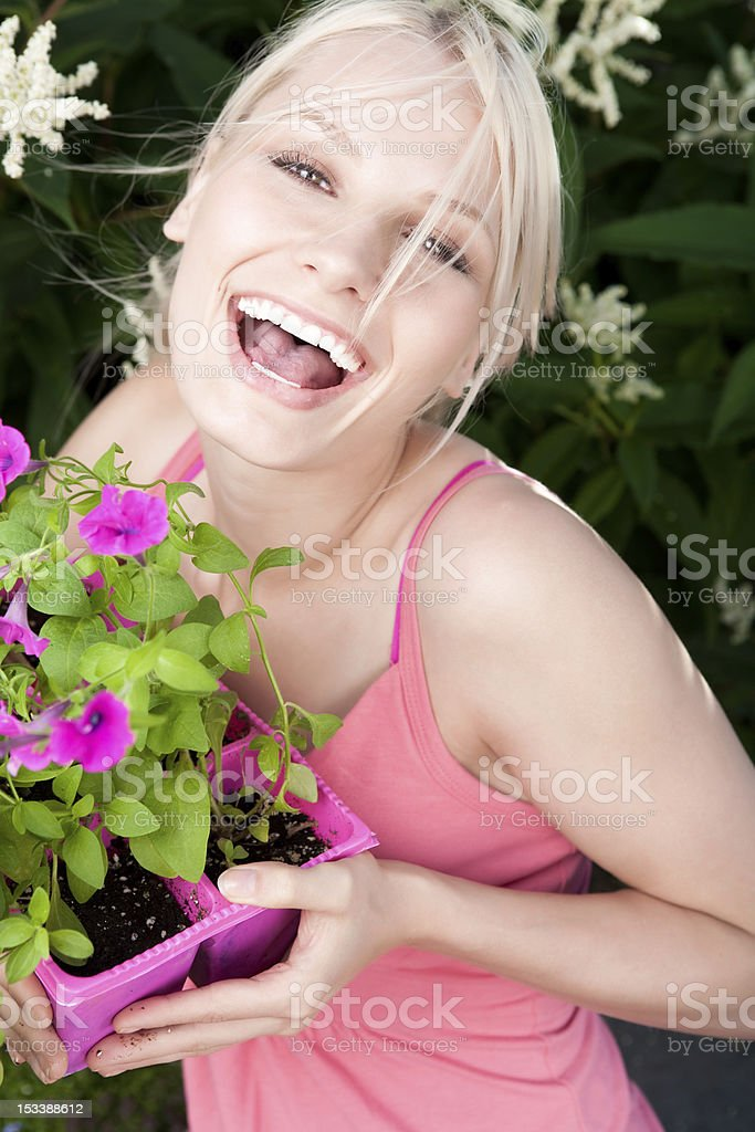 Smiling young woman holding tray of petunias royalty-free stock photo