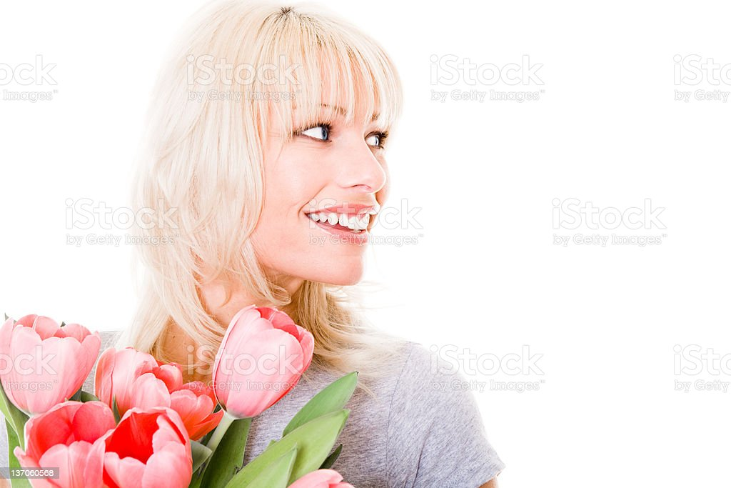 Smiling young woman holding tulips looking away royalty-free stock photo