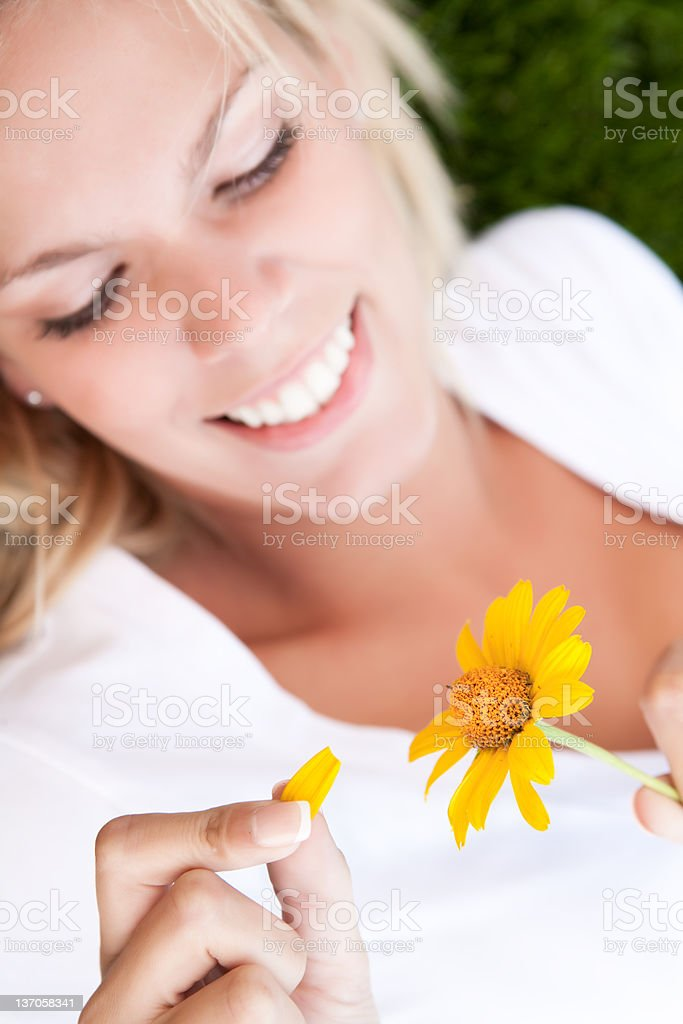 Smiling young woman holding yellow daisy royalty-free stock photo