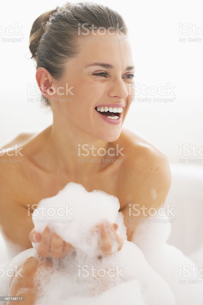 smiling young woman in bathtub with foam stock photo