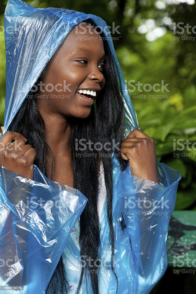 Smiling young woman in blue rain poncho stock photo