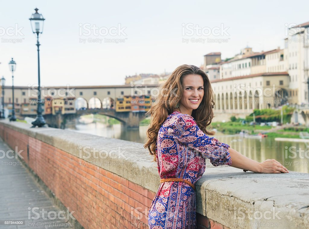 Smiling young woman in dress on embankment near Ponte Vecchio stock photo