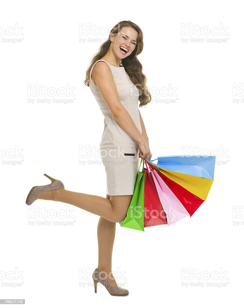 Smiling young woman in dress with shopping bags royalty-free stock photo