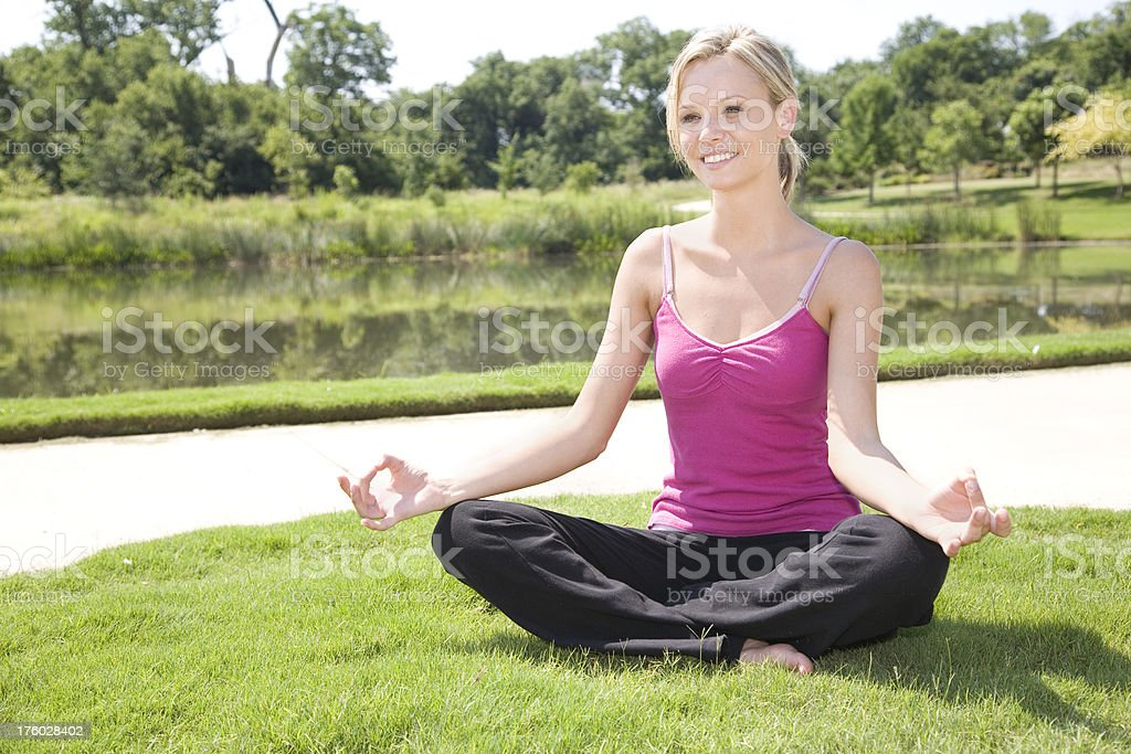 Smiling Young Woman in Meditation Pose at a Park royalty-free stock photo
