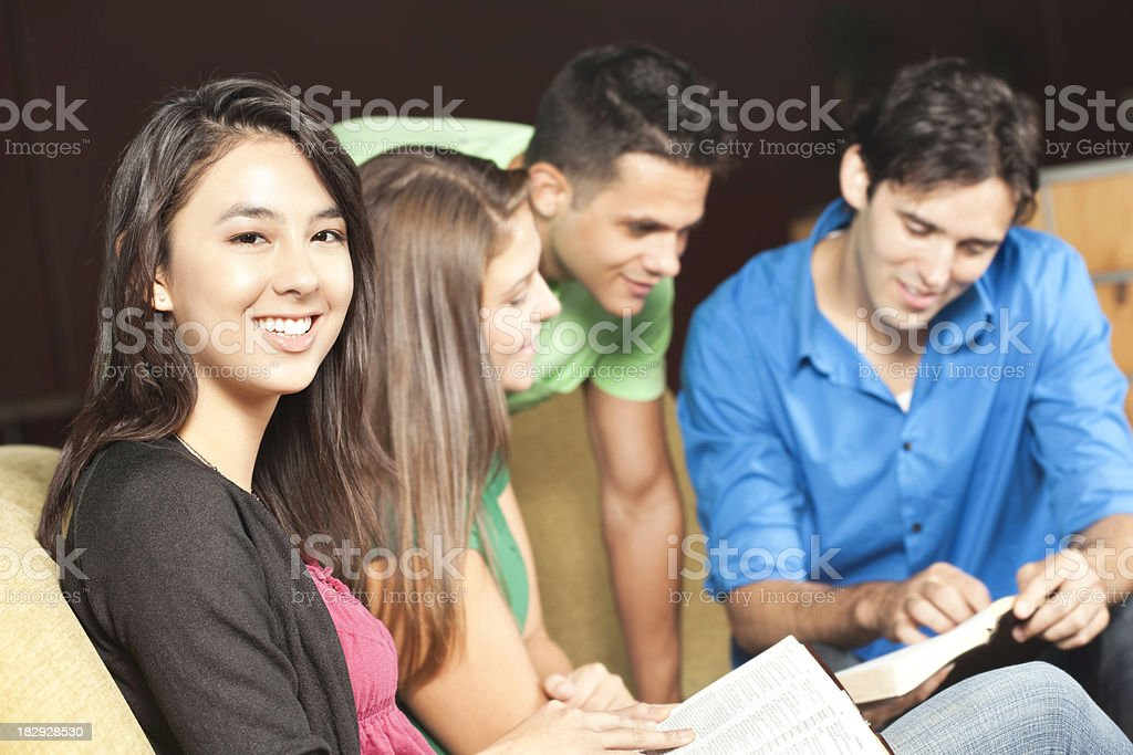 Smiling Young Woman In Middle of Bible Study Group stock photo