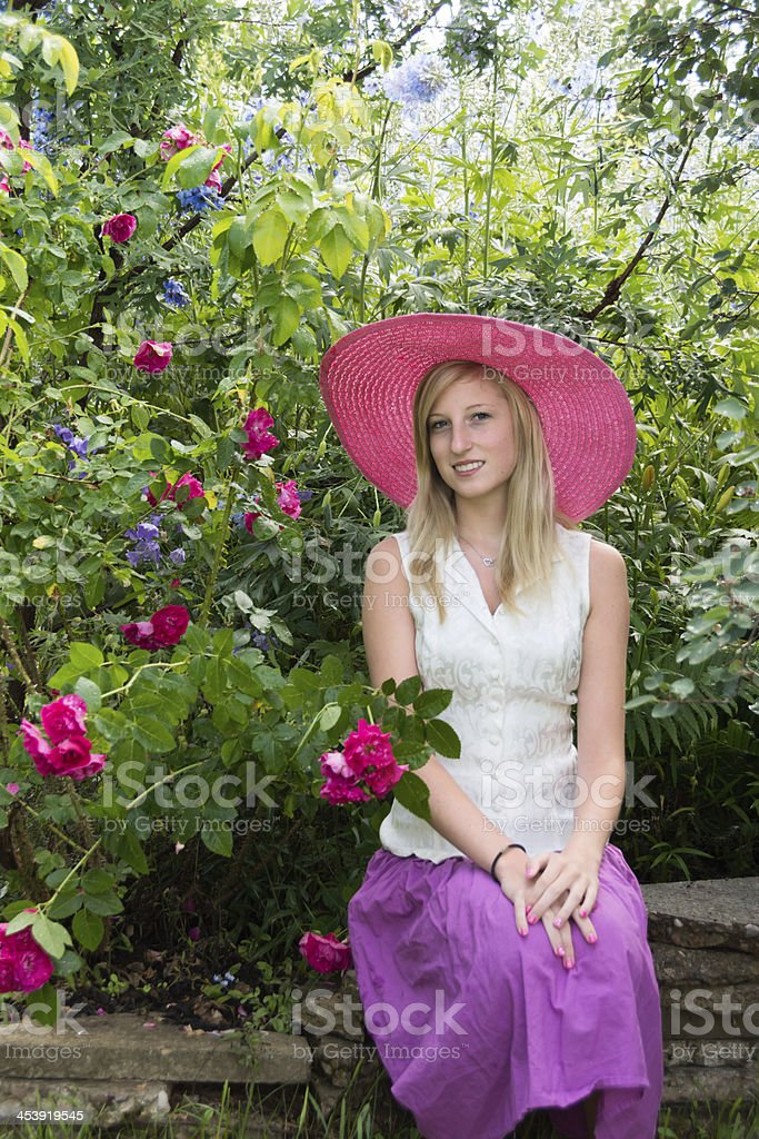 Smiling young woman in ornamental garden. royalty-free stock photo