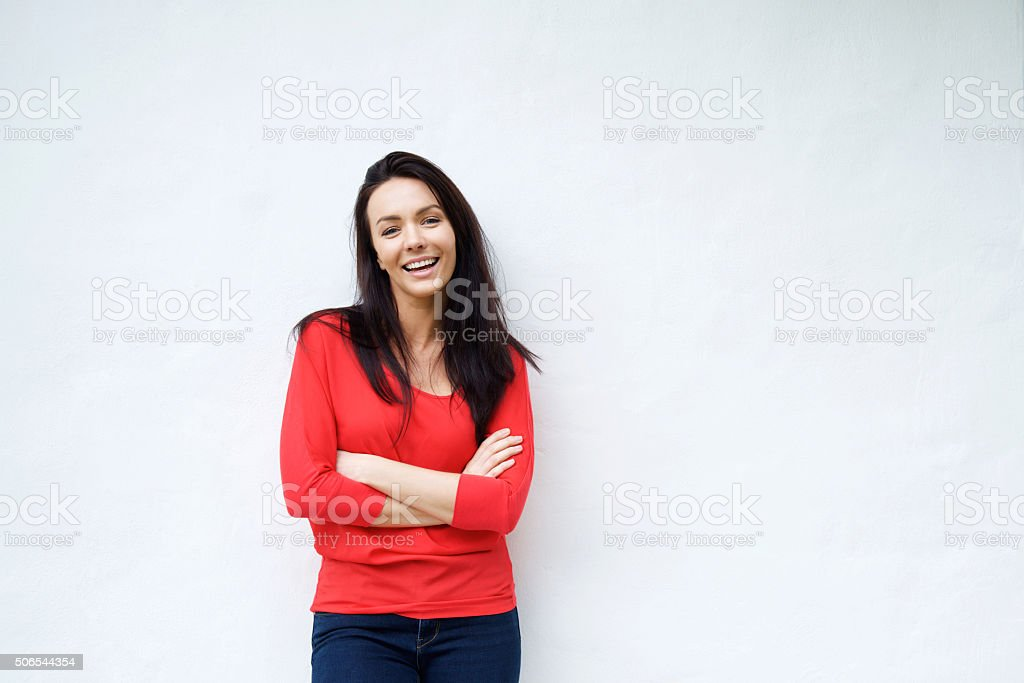 Smiling young woman in red shirt smiling against white background stock photo