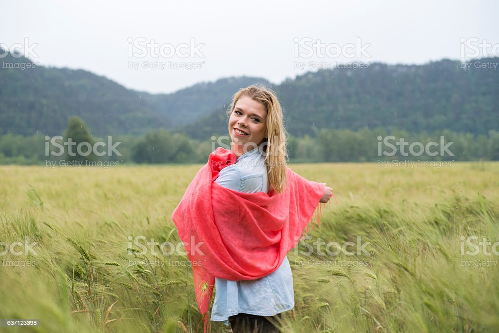 Smiling young woman in wheat field stock photo