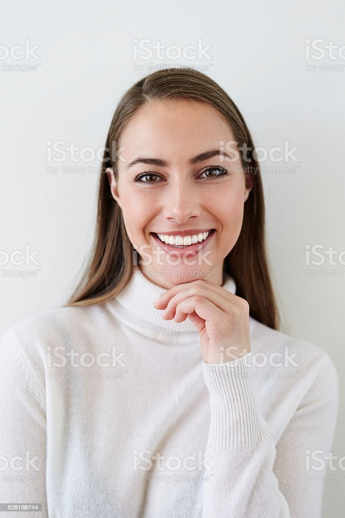 Smiling young woman in white top, portrait stock photo