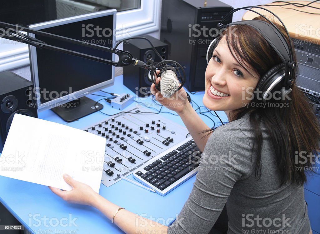 Smiling young woman inside radio cabin holding microphone stock photo