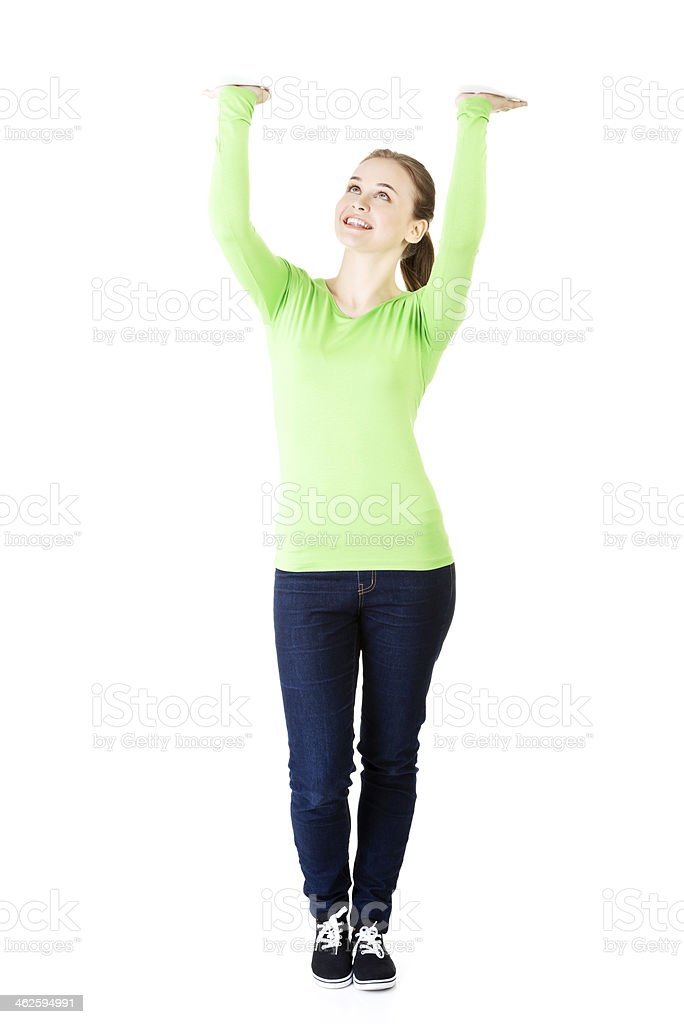 Smiling young woman is holding something abstract above her head stock photo