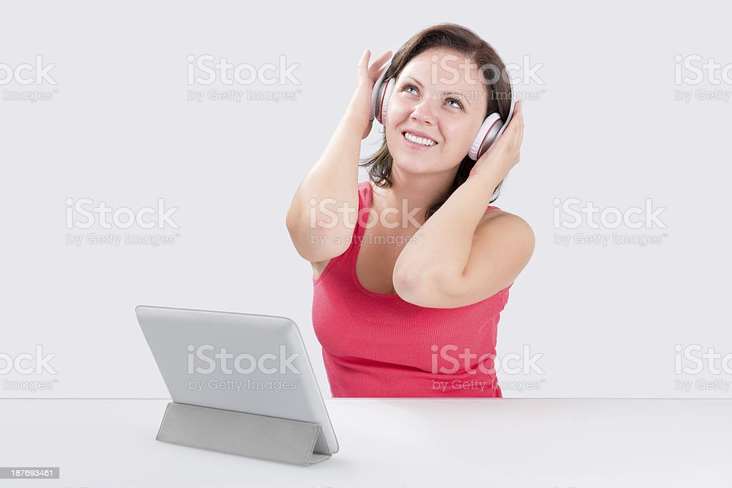 Smiling young woman is listening to music stock photo