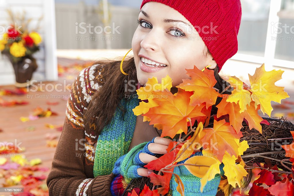 Smiling young woman leaning holding autumn wreath royalty-free stock photo