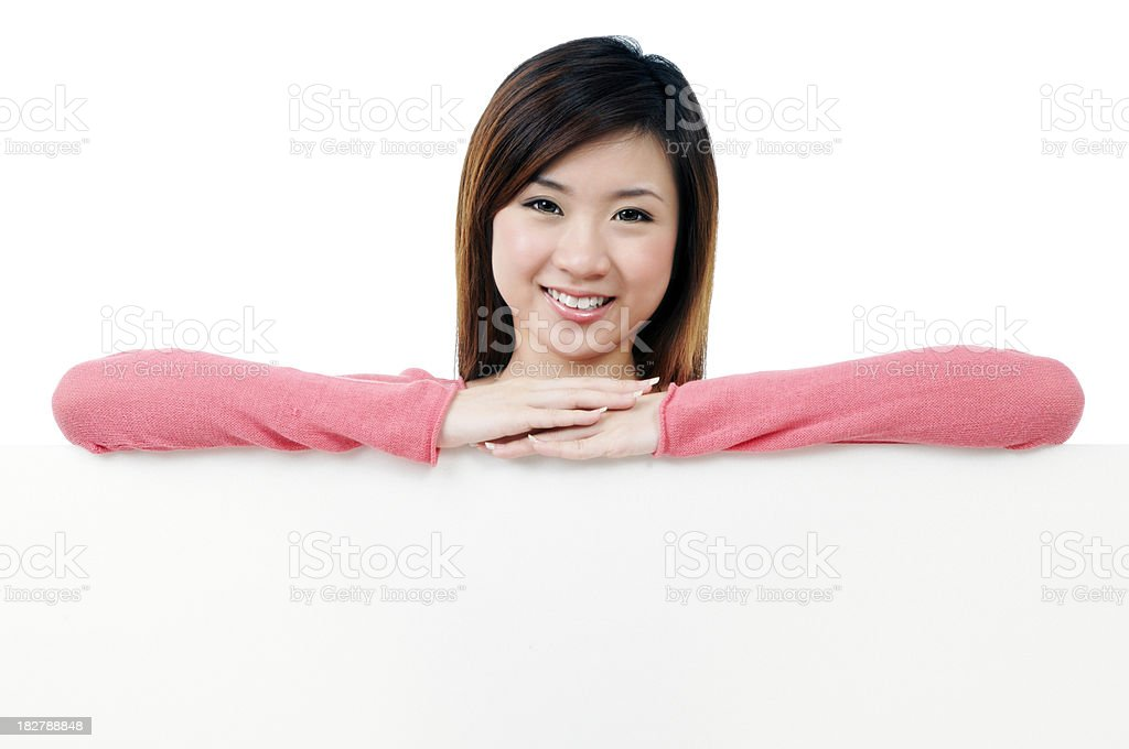Smiling young woman leaning on blank billboard stock photo
