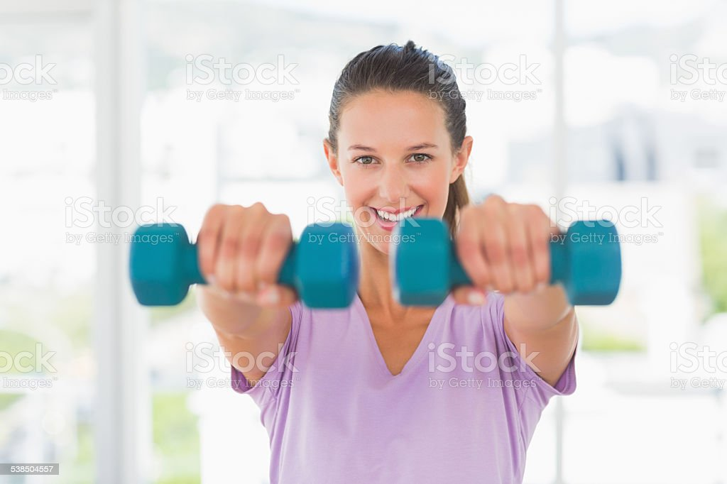 Smiling young woman lifting dumbbell weights stock photo
