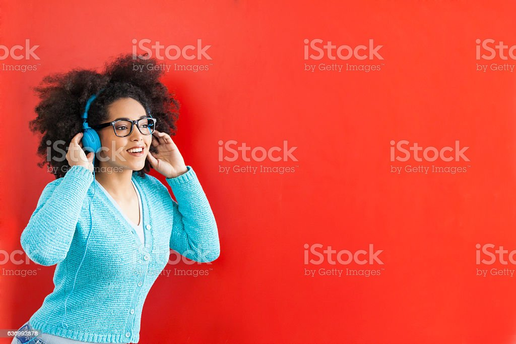 Smiling young woman listening music on red background stock photo