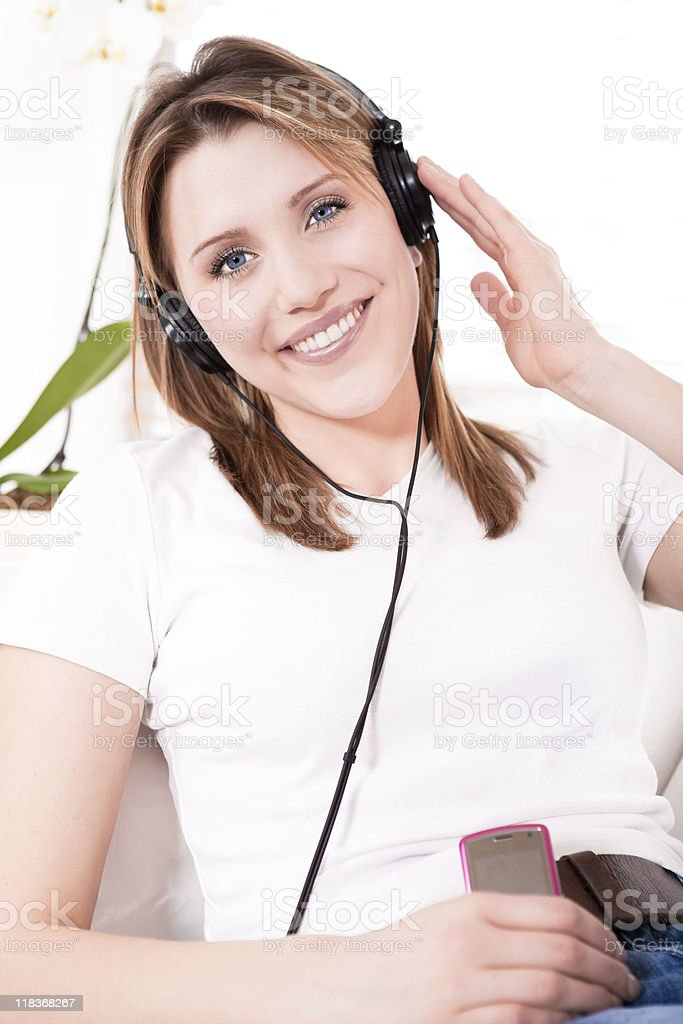 Smiling young woman listening to her headphone royalty-free stock photo