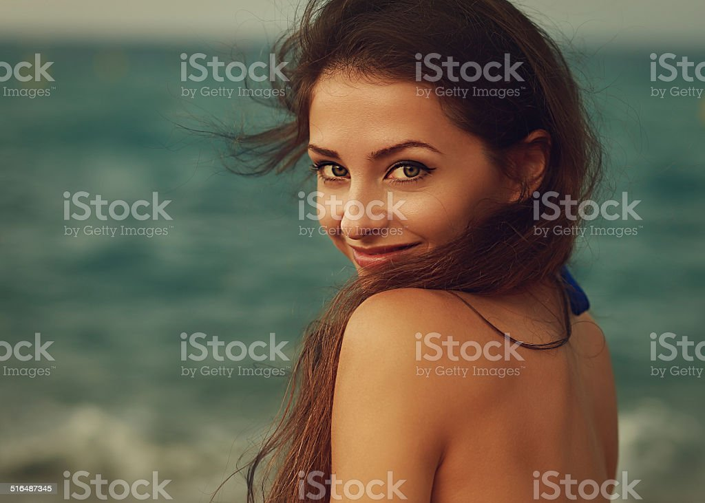 Smiling young woman looking happy on sea background. Closeup stock photo