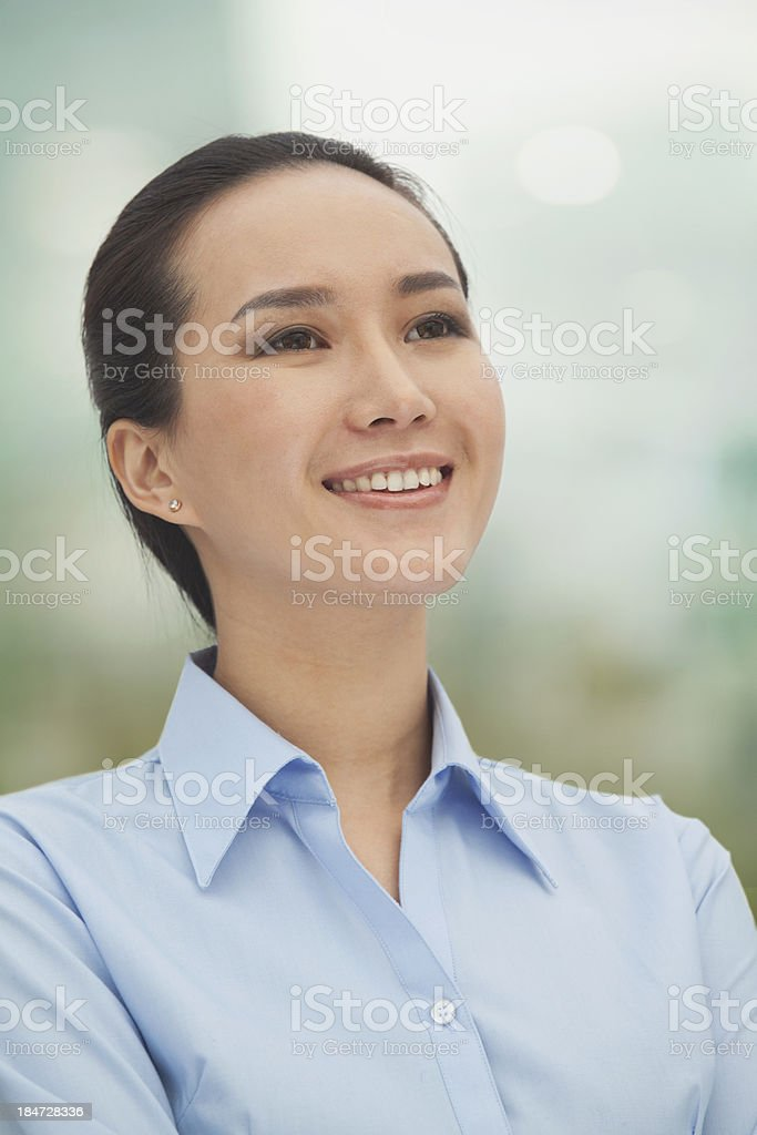 Smiling young woman looking up royalty-free stock photo