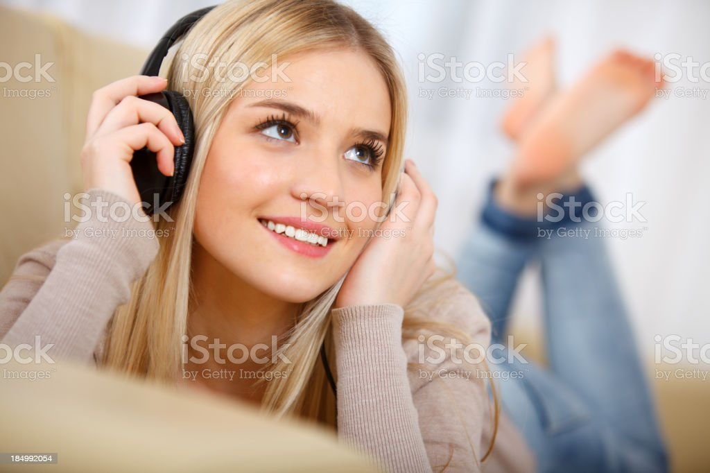 Smiling young woman lying on couch listening to music royalty-free stock photo