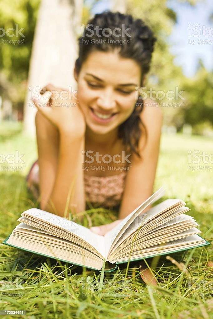 Smiling young woman lying on front reading royalty-free stock photo