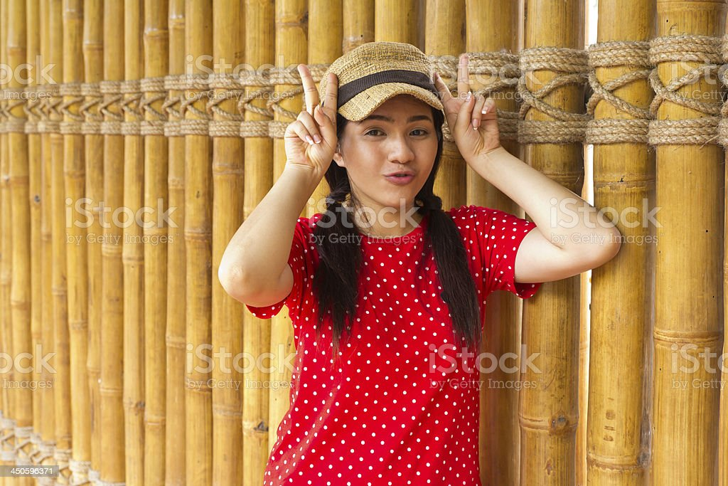 Smiling young woman makes two peace signs with hands royalty-free stock photo