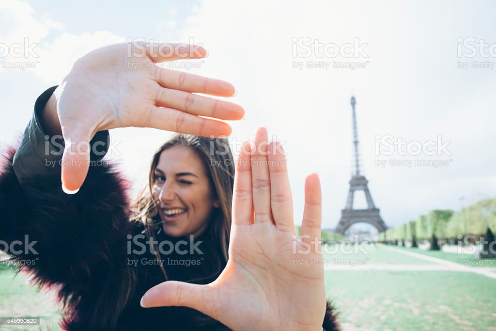 Smiling young woman making finger frame stock photo