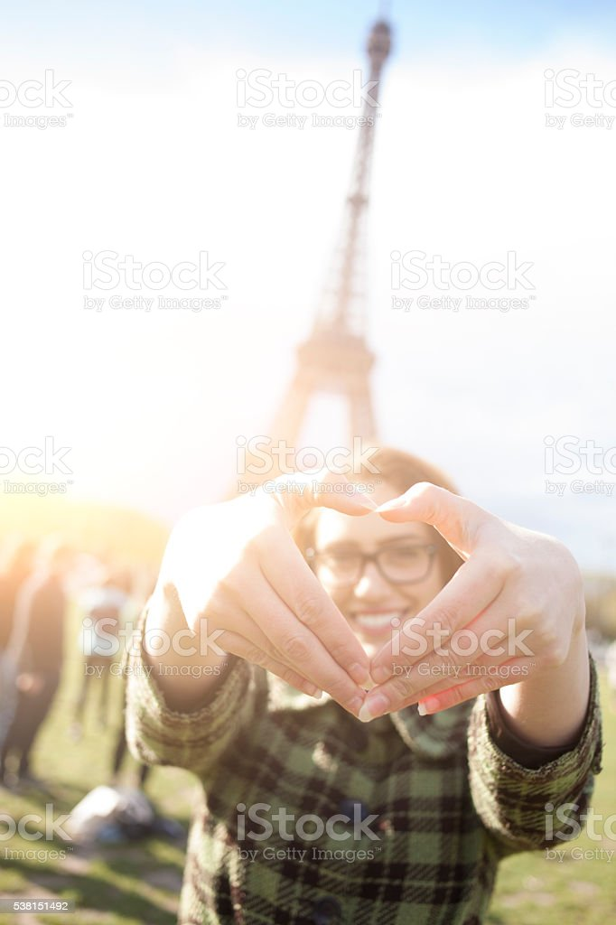 Smiling young woman making heart shape with fingers stock photo