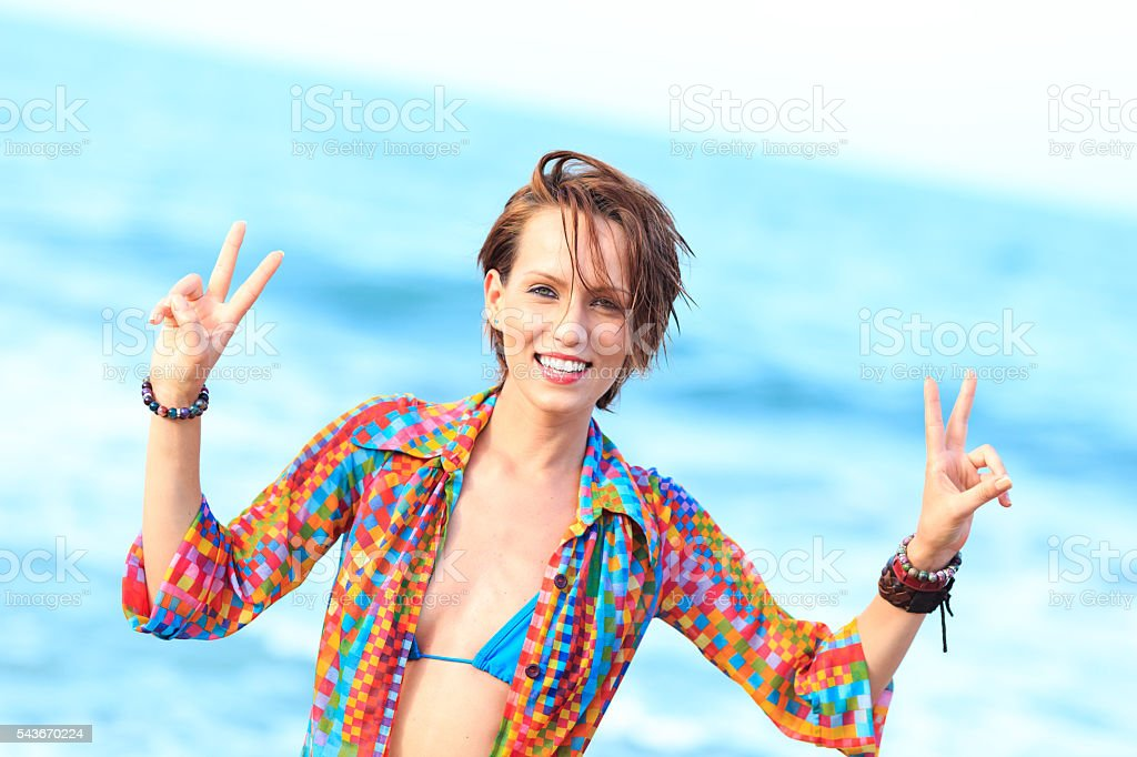 Smiling young woman making peace sign on beach stock photo