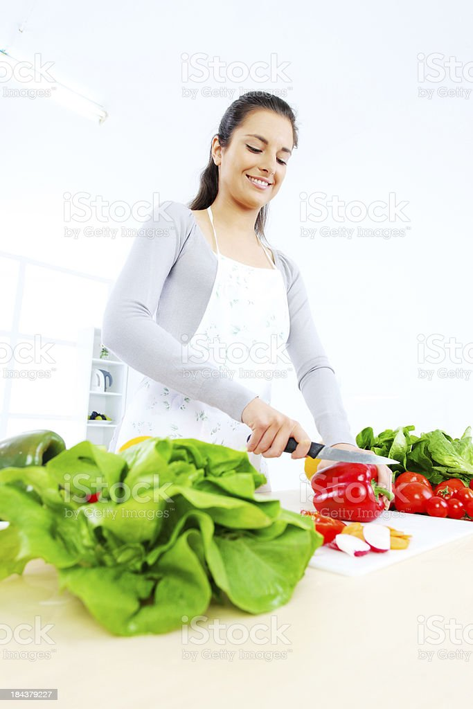 Smiling young woman making salad in the kitchen. royalty-free stock photo
