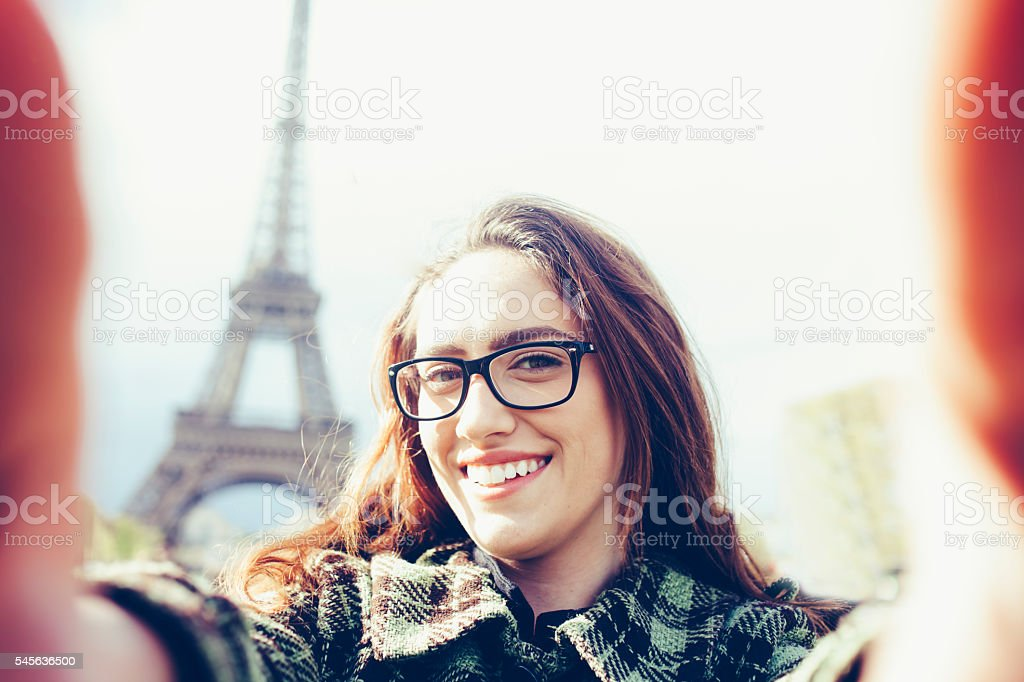 Smiling young woman making selfie in front Eiffel tower stock photo