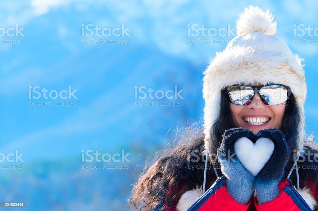 Smiling young woman making snow heart in winter mountain stock photo