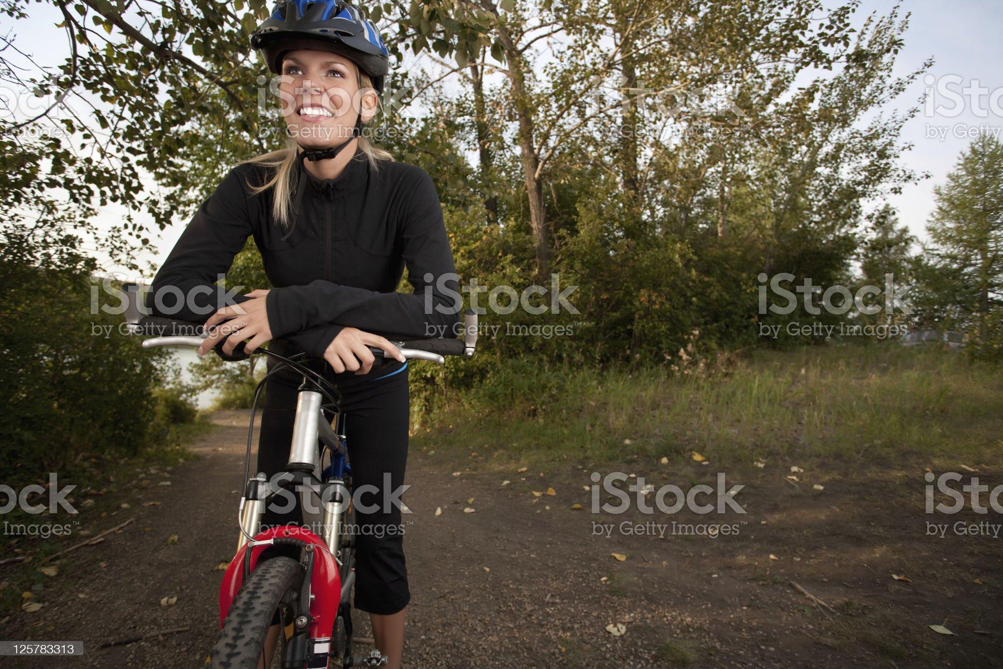 Smiling young woman mountain biking royalty-free stock photo
