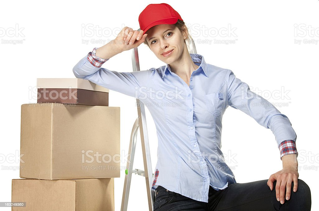 Smiling young woman near a pile of boxes royalty-free stock photo