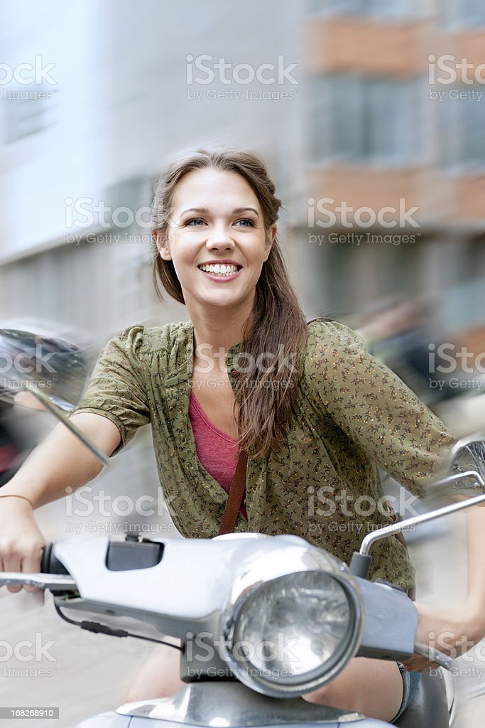 smiling young woman on scooter royalty-free stock photo