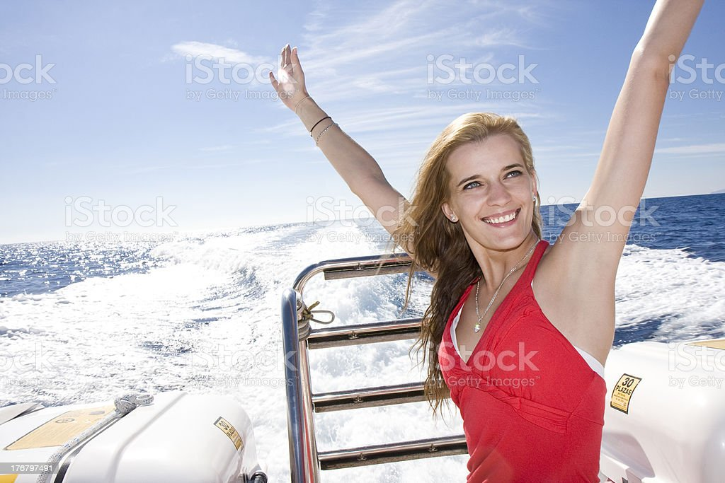 Smiling young woman on yacht in red bathing suit stock photo