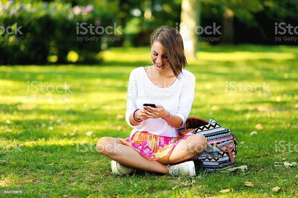 Smiling young woman or teenage girl messaging on smartphone stock photo