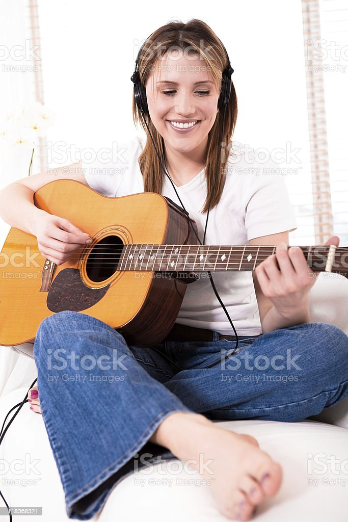 Smiling young woman playing the guitar royalty-free stock photo