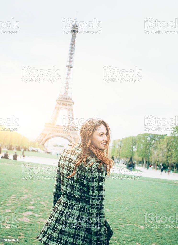 Smiling young woman posing in front of Eiffel tower stock photo