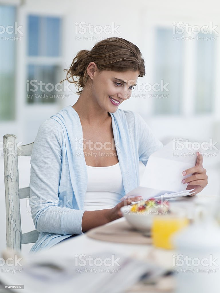 Smiling young woman reading a letter at breakfast table royalty-free stock photo