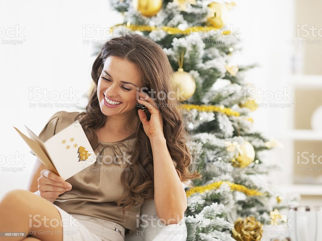Smiling young woman reading card near christmas tree stock photo
